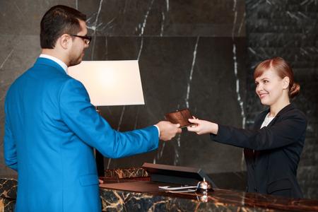 passeport: Arrivée processus. Mise au point sélective d'un bel homme d'affaires en costume bleu qui passe son passeport à un sourire de la réceptionniste derrière le comptoir de l'hôtel Banque d'images