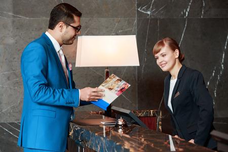 Hotelinformation zur Verfügung. Gut aussehende Geschäftsmann, der ein Informationshalter copy fragt Rezeption über Dienstleistungen des Hotels Lizenzfreie Bilder