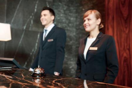 Kann ich Ihnen helfen. Selektiven Fokus auf Hotelservice-Glocke mit weiblichen und männlichen Rezeptionisten hinter der Theke in verschwommen setzen in Uniform stehend