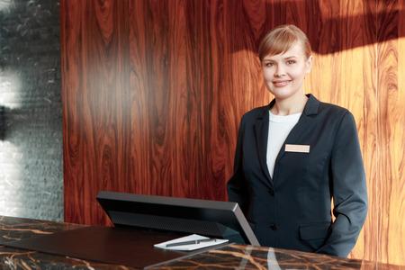recepcionista: Hermoso estilo recepcionista del hotel de pie detr�s de la mesa de servicio en un pasillo del hotel mirando a un cliente con una sonrisa