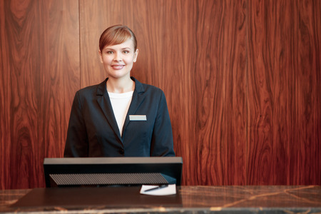 counter service: Beautiful stylish hotel receptionist standing behind the service desk in a hotel lobby looking at a guest with a friendly smile