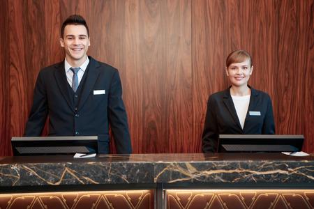 recepcion: Bienvenido al hotel. Recepcionistas hombres y mujeres de pie en el mostrador de recepci�n con el fondo de madera recibe a los hu�spedes con una sonrisa