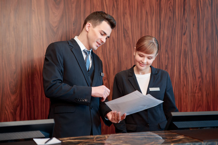 reception counter: Reception at work. Male receptionist shows business papers to the female receptionist to discuss operating activity Stock Photo