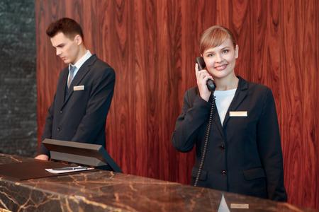 recepcionista: Recepci�n en el tel�fono. Recepcionista sonriente joven en uniforme negro de contestar la llamada en el mostrador del hotel Foto de archivo