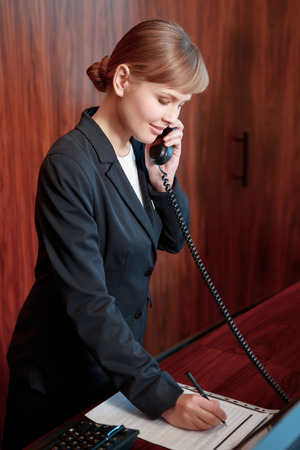 confirmed: Booking confirmed. Young attractive female receptionist answering the call and making notes at the notepad by the reception desk Stock Photo