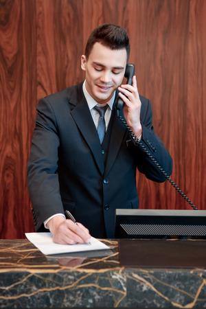Helyfoglalás megerősítette. Fiatal jóképű férfi recepciós fogadja a hívást és jegyzeteket készít a jegyzetfüzetbe a recepciónál Stock fotó
