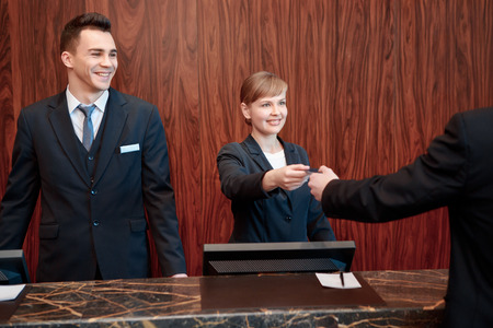 hotel lobby: Here is your key.  Receptionists welcome guest with a smile while giving a key
