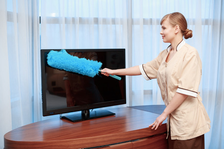 carved letters: No trace of dust. Hotel maid in beige uniform dusting with a feather duster TV screen in hotel room