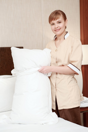 room service: Hotel room service Vertical closeup of a maid changing bedclothes on the pillow