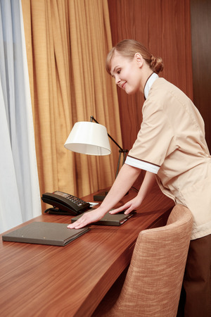 room service: Room service. Maid checking well-arranged stationery and hotel information kit at the room table