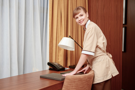 carved letters: Room service. Maid checking well-arranged stationery and hotel information kit at the room table
