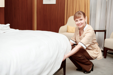 luxury hotel room: Perfect order. Smiling maid tidying up bed and cleaning luxury hotel room