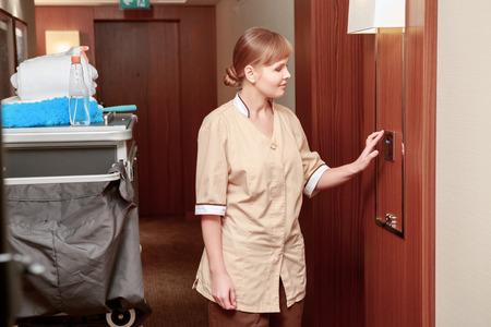 sirvienta: Tiempo de servicio de habitaciones. Sonriendo camarera de hotel en uniforme de color beige comprueba los indicadores del clima en el hall del hotel de pie justo al lado del carro de limpieza Foto de archivo