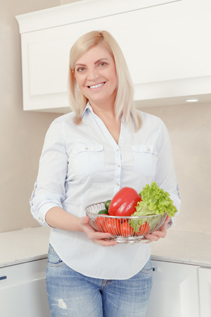 beautiful middle aged woman: Healthy Lifestyle. Beautiful middle aged woman in casual clothes holding a plate with vegetables and smiling