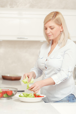 beautiful middle aged woman: Vegetarian cuisine. Closeup on beautiful middle aged woman slicing vegetables for the salad