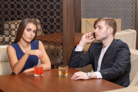 poner atencion: Hacer negocios. Joven hablando por tel�fono mientras que su novia se ve aburrido y decepcionado como �l no presta atenci�n a su