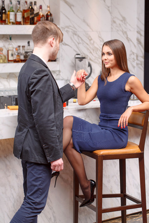 dance bar: Invitation to dance. Young man inviting his girlfriend to dance while she is sitting on the chair at the bar counter