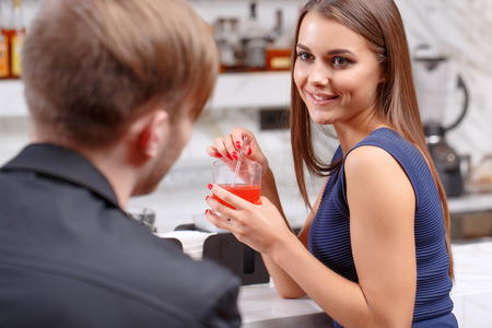 Intimate talks. Selective focus on a young smiling woman talking to the man sitting in front of her in the bar