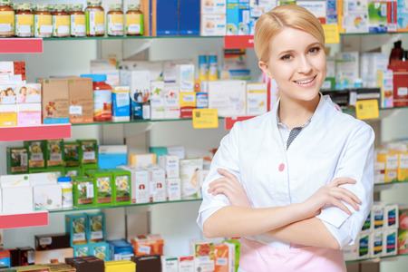 pharmacy store: Everything for the best therapy. Young smiling druggist in white uniform standing with her arms crossed near the show case of a drug store Stock Photo