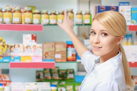 farmacia: Siga la receta. Farmac�utico rubia joven que toma la medicina y las drogas de los estantes de la farmacia
