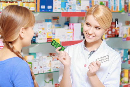 suggests: Blister or full pack. Young smiling pharmacist suggests to the customer two blisters of pills Stock Photo
