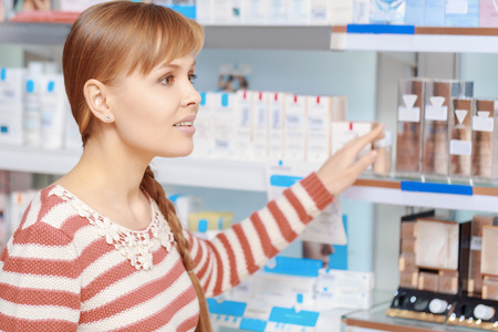 addresses: Health care consultancy. Young attractive woman addresses someone in a drugstore in terms of beauty care products