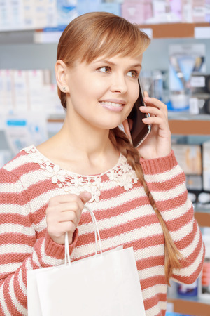 consultancy: Phone consultancy. Close-up of a young smiling woman talking over the phone in a pharmacy shop