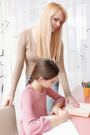 exercise book: Tutoring humanities. Beautiful blond mother helping her teenage daughter with the home task looking into the book while the girl is writing in her exercise book