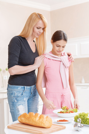 keep fit: Keep fit. Beautiful mother and daughter looking at the dish with salad standing on a kitchen table