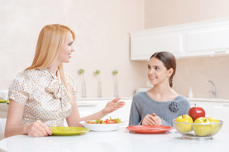 lunchtime: Lunchtime conversation. Charming cheerful mother and pretty daughter talking and eating salad at lunch in the kitchen Stock Photo