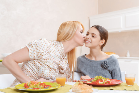 blonde teenage girl: Loving mother. Beautiful mother kissing her cute teenage daughter as they are having lunch together Stock Photo