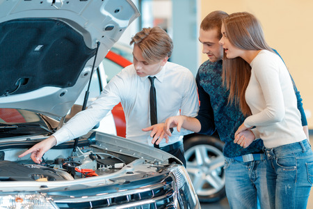describes: Really powerful and fuel efficient engine. Sales consultant pointing to the engine of the vehicle describes technical characteristics of the car to the young couple in the showroom