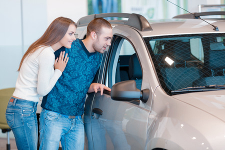 rental: It is beautiful. Smiling young couple standing alongside a car and leaning against it watch at the interior of a new car Stock Photo