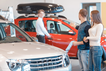 suggests: Just have a look. Salesman suggests young couple to explore another vehicle of the different color displayed at the showroom in selective focus