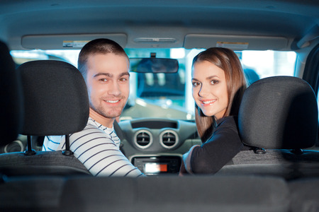 Ready for the journey. Young cute couple sitting on the front seat of the new vehicle and turning backward to the back seat to view car interior