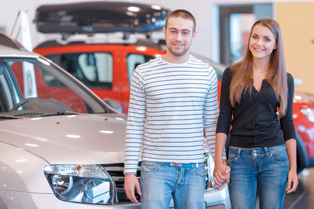 intend: This is a perfect car for young family. Attractive couple holding each other hands stand by a new car they intend to buy with showroom view in blurry
