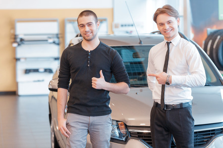 customer: Best service ever. Male customer showing his thumb up and young smiling sales consultant pointing to the customer show delight about the purchase of a new car with a showroom view on the background Stock Photo