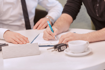 Sign up and drive. Cropped view in selective focus of the hands of a male customer signing a contract and sales consultant sitting nearby. White cup of coffee, keys, clipboard and nameplate copyspace are placed on the table