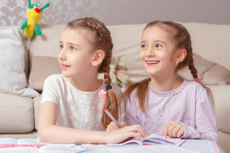 Small princesses. Small cheerful girls entertaining with writing in their diaries and smiling photo
