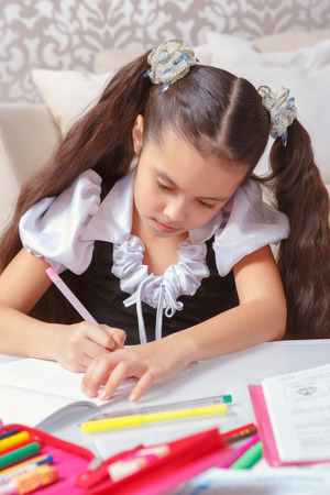 decent: Decent school kid. Top view of a small girl with long dark hair writing in her exercise book sitting at home table with many markers and pens on it