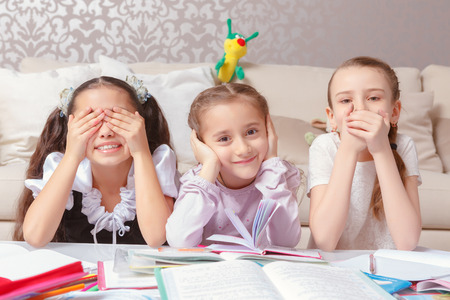 Three wise monkeys. Three small schoolgirls jokingly pretend three wise monkeys closing their eyes, ears and mouth in the meaning of see no evil, hear no evil, speak no evil Stock Photo