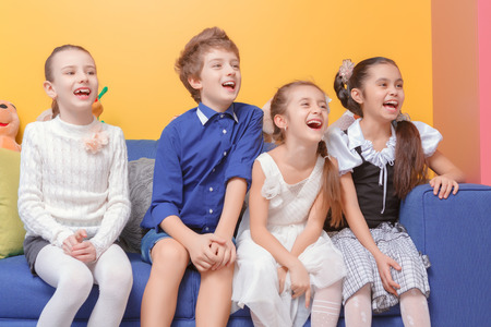 laughing out loud: Laughing out loud. Cute school children laughing loudly when sitting on the sofa at kids room Stock Photo