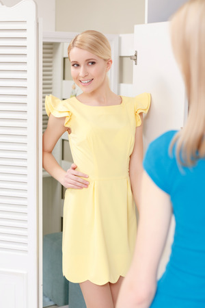 blonde teenage girl: Festive look. Close-up of a young smiling blonde teenage girl trying yellow dress in a dressing room and demonstrating her look to her friend