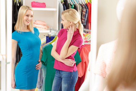Perfect match. Shop assistant is talking to a smiling customer wearing a new blue dress photo