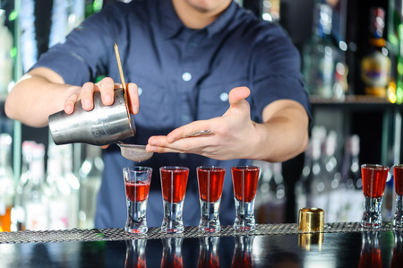 nightclub bar: Night club. Barman using a shake mixer cocktails and drinks in nightclub, bar or pub Stock Photo