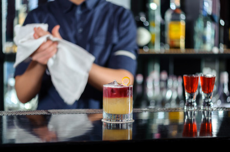 great job: Great job. Selective focus on beautiful red and yellow cocktail on the counter while bartender drying hands with a towel stands behind the bar counter Stock Photo