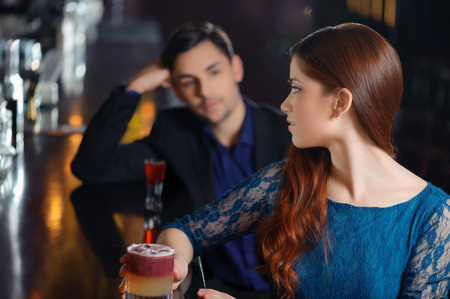 Close-up of a young attractive woman turning back towards a man sitting by the bar counter
