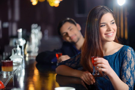 flirt: Sweet flirt. Smiling young woman delighted with a attention of a young man sitting near her at the bar