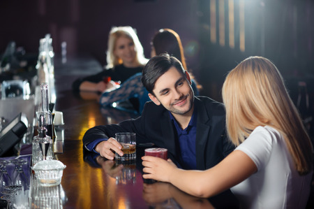 barra: Larga noche. Pareja interactuar con alegr�a por la barra de bar en la discoteca o restaurante Foto de archivo