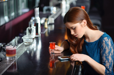 single woman: Esperando a un amigo. Mujer atractiva joven que mira la pantalla de su teléfono sentado en el bar con un cóctel